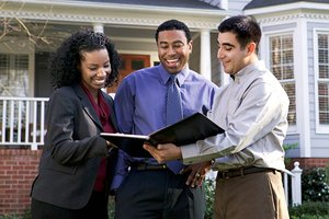 Couple & Realtor in front of house